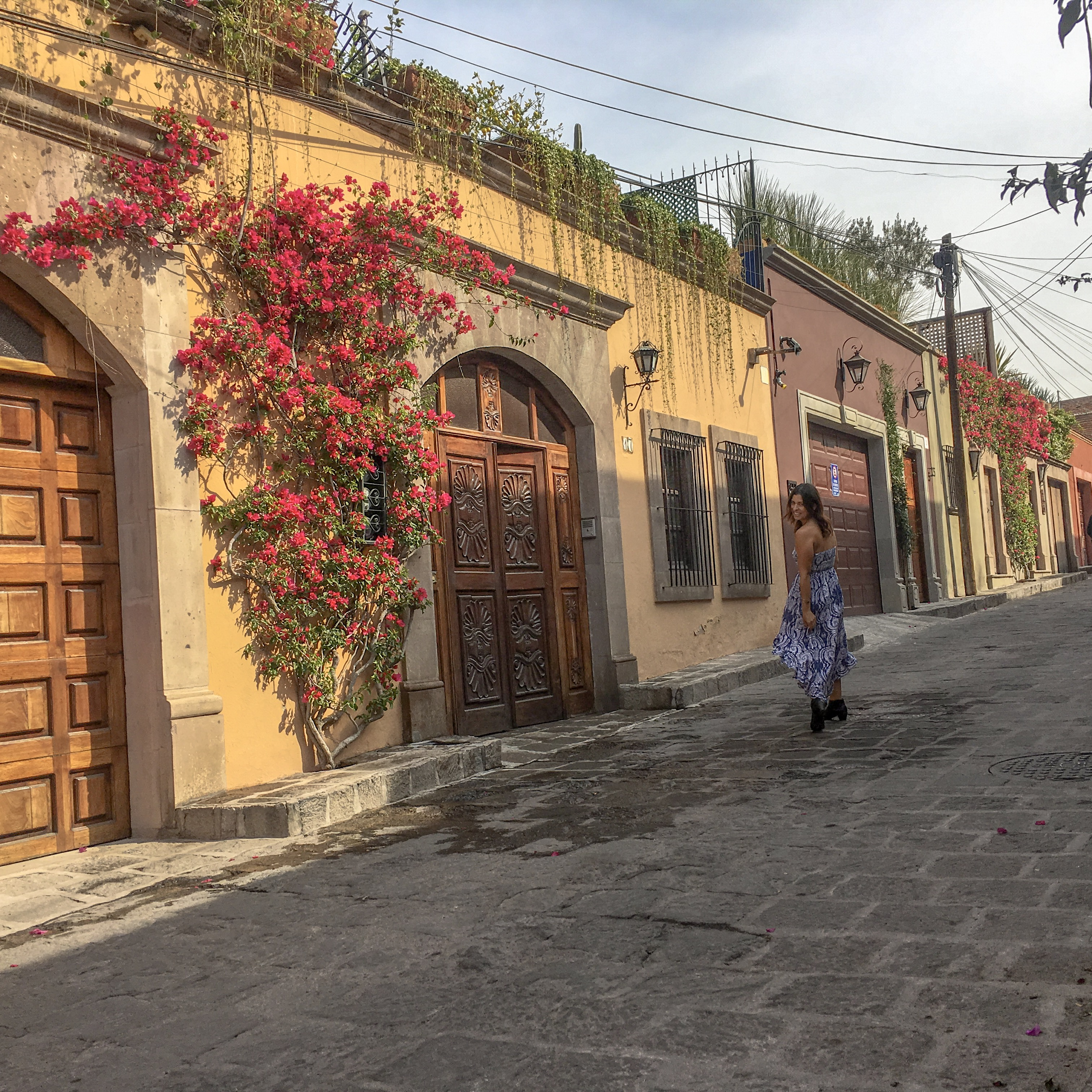 woman walking down cobblestone street san miguel de allende mexico