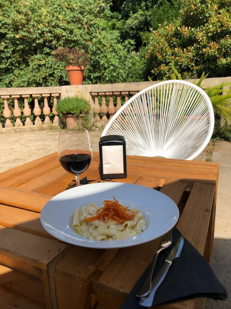 outdoor patio table with pasta and wine