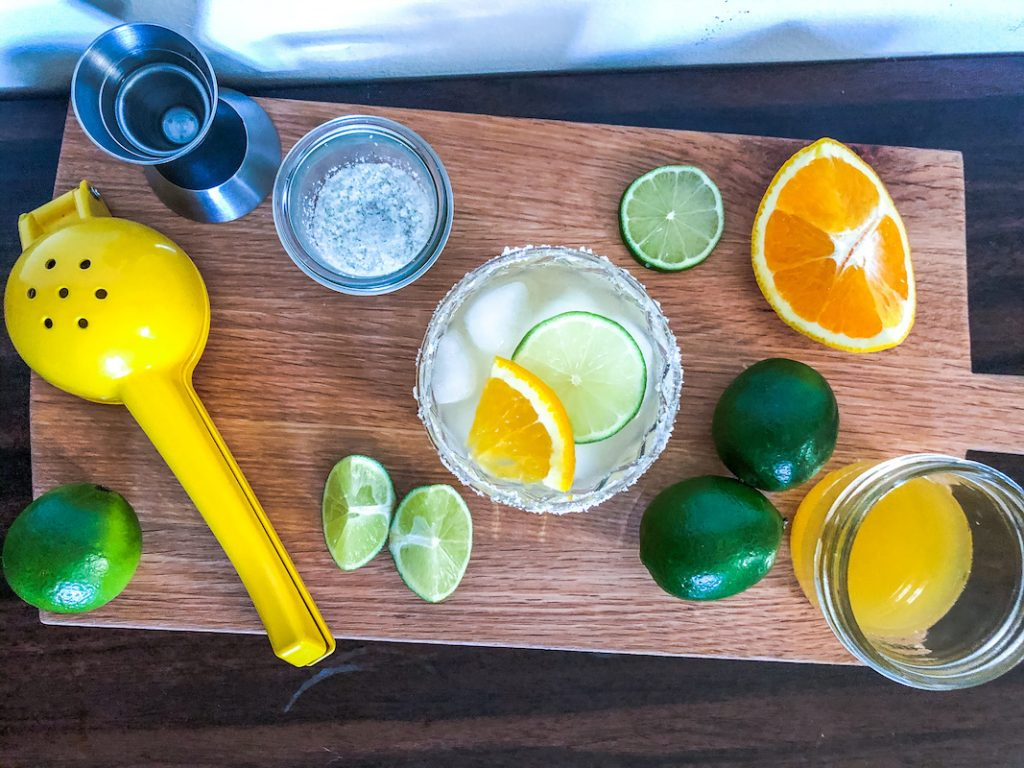 skinny margarita with tools and ingredients citrus squeezer jigger salt lime oranges
