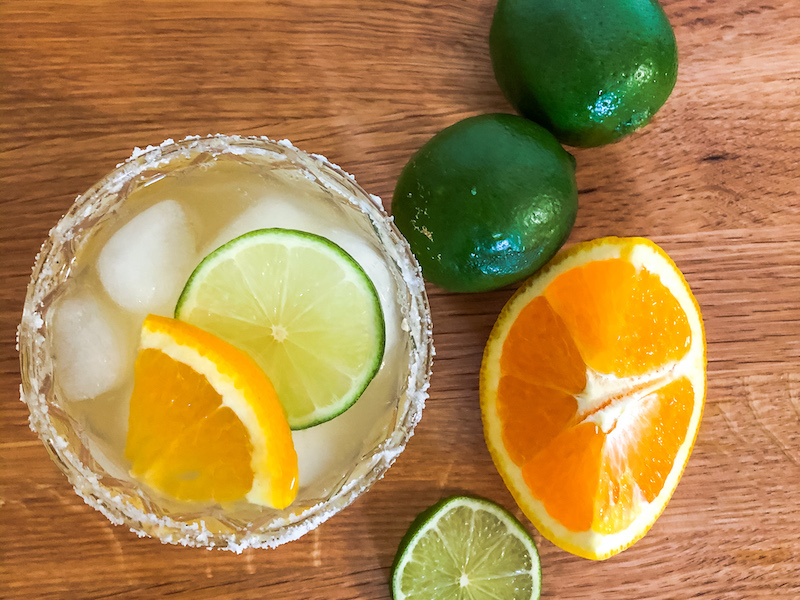 aerial view of skinny margarita with salted rim and lime and orange wedges