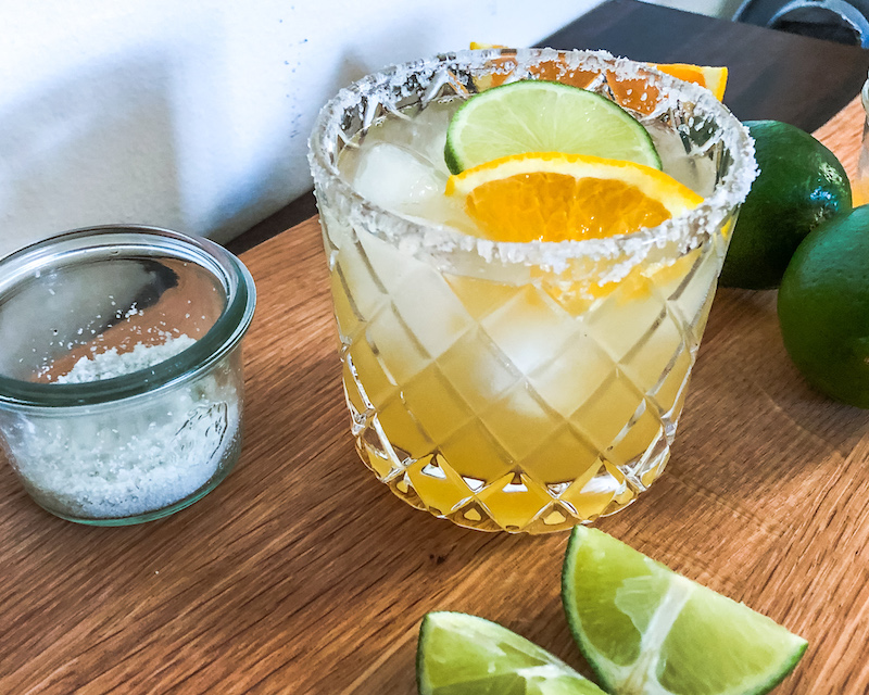 skinny margarita with salted rim and lime wedges