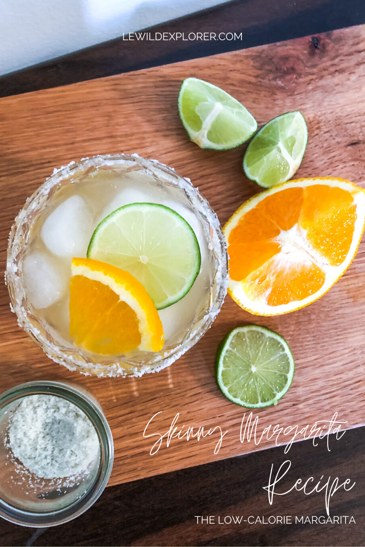 skinny margarita cocktail with salted rim and lime and orange wedges