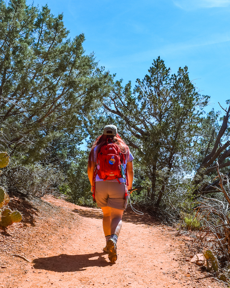 woman hiking with red packpack