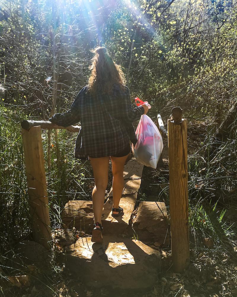 woman picking up trash hiking