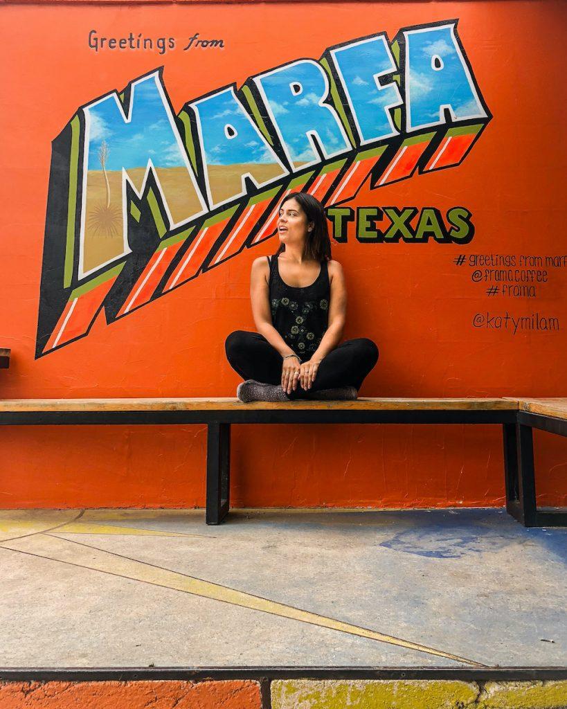 woman at greetings from marfa mural