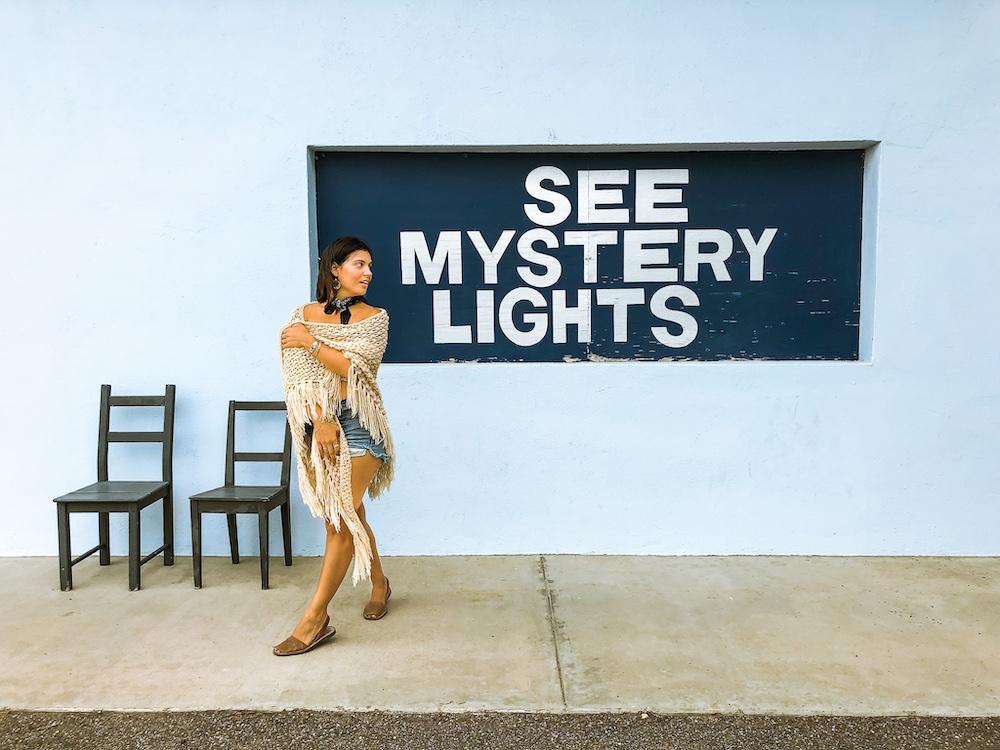 woman at see marfa lights sign