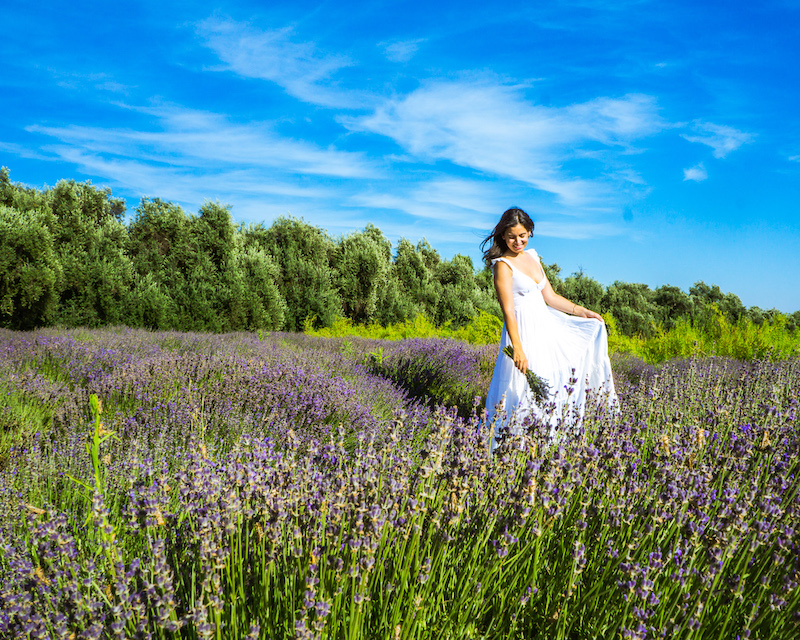 woman in white dress holding lavender bouquet on field