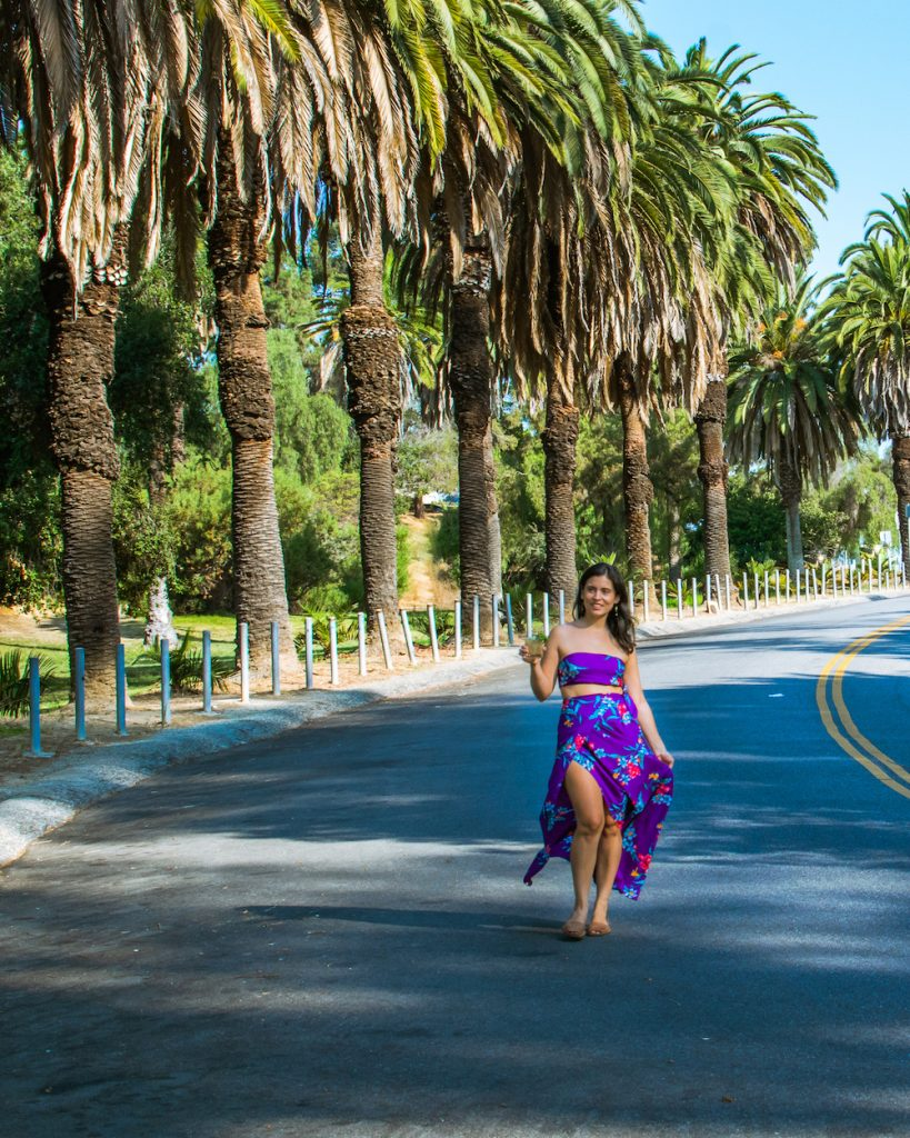 woman in polynesian sarong and top with mai tai palm trees in background