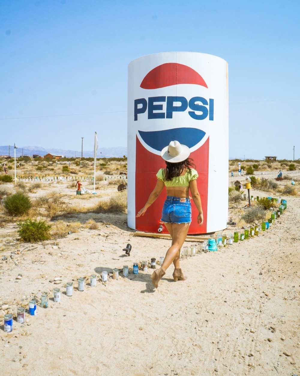 woman at Glass Outhouse Art Gallery 29 palms pepsi sculpture