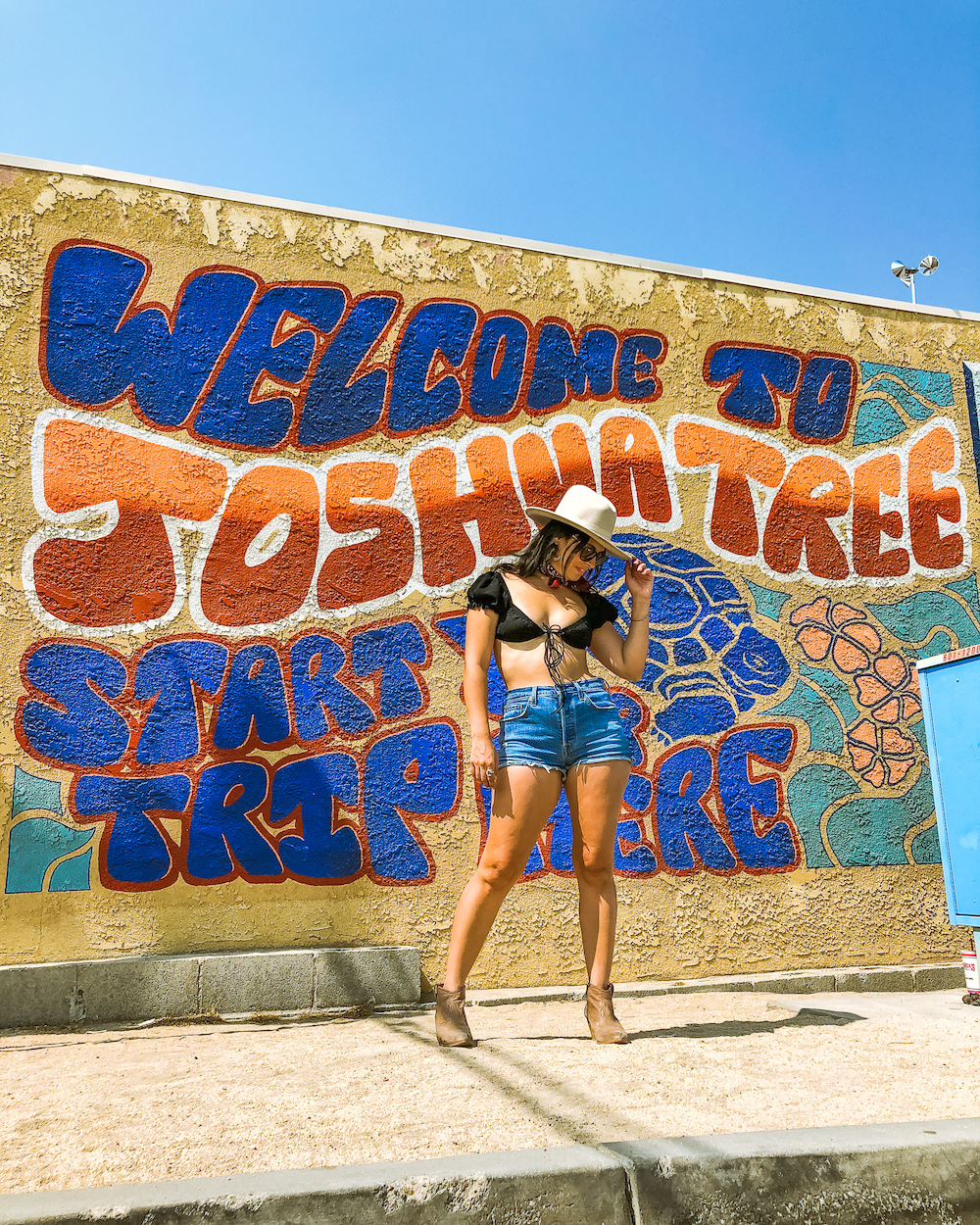 woman at welcome to joshua tree mural
