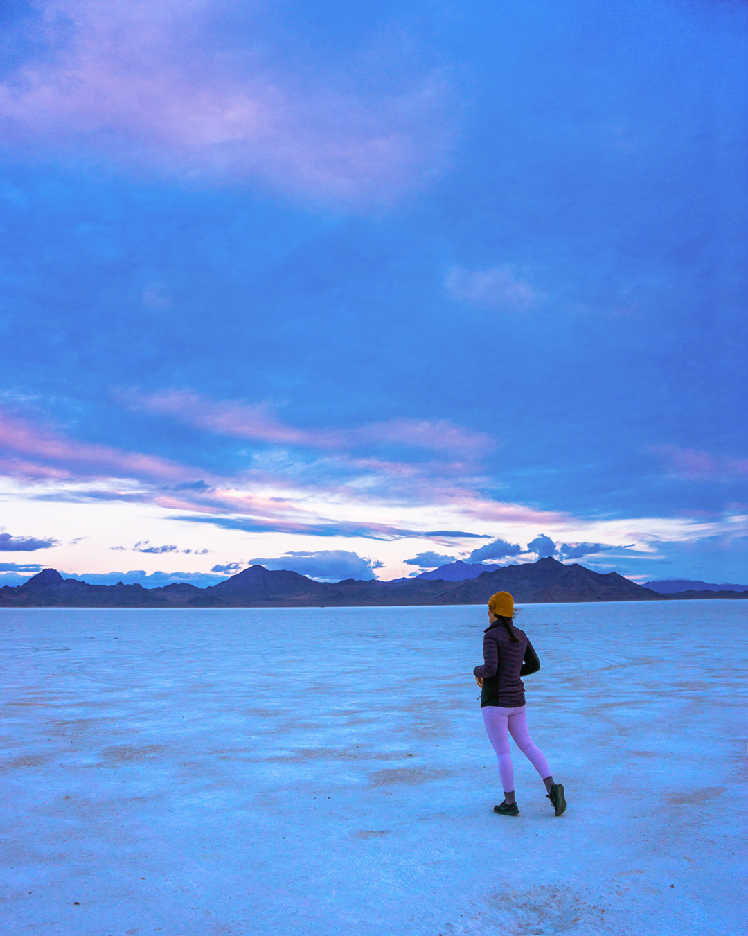 woman at bonneville salt flats in utah at sunrise with mountains in background