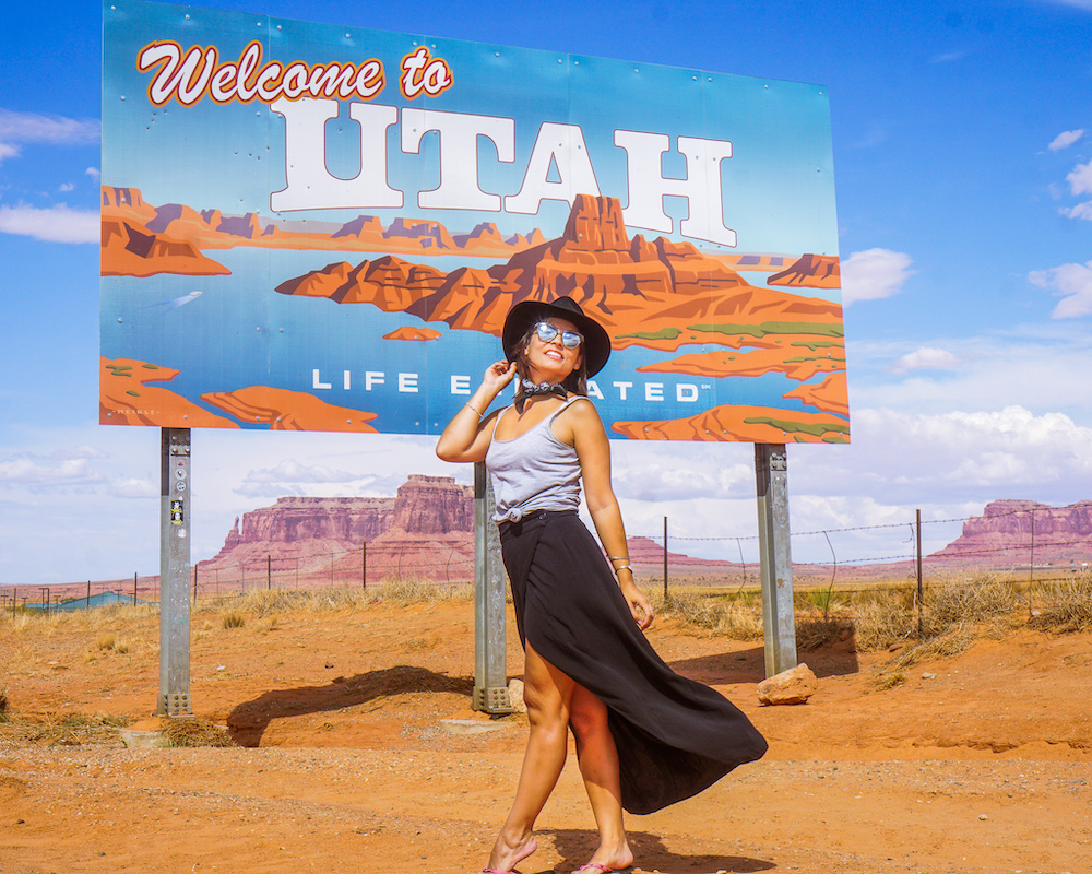 woman standing for photoshoot at welcome to utah sign near monument valley of the gods