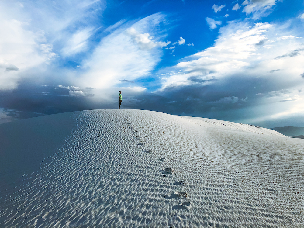 man on top of white sand dunes new mexico