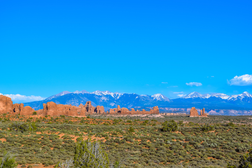 view of windows section arches national park with snow capped mountains in the distance