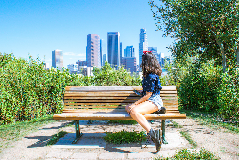 woman sitting with phone in hand at dtla skyline view from vista hermosa park los angeles