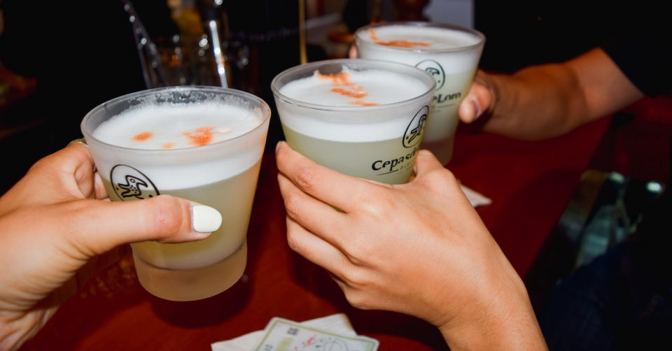 friends cheers with pisco sour cocktails in hand
