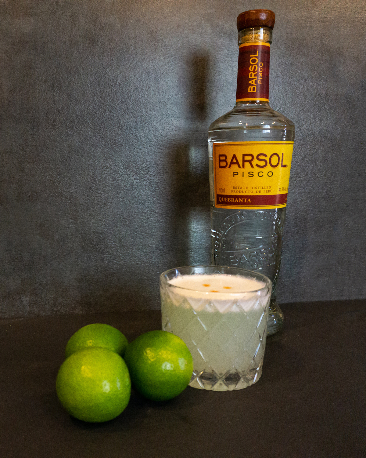 pisco sour cocktail in rocks glass with lime and bottle