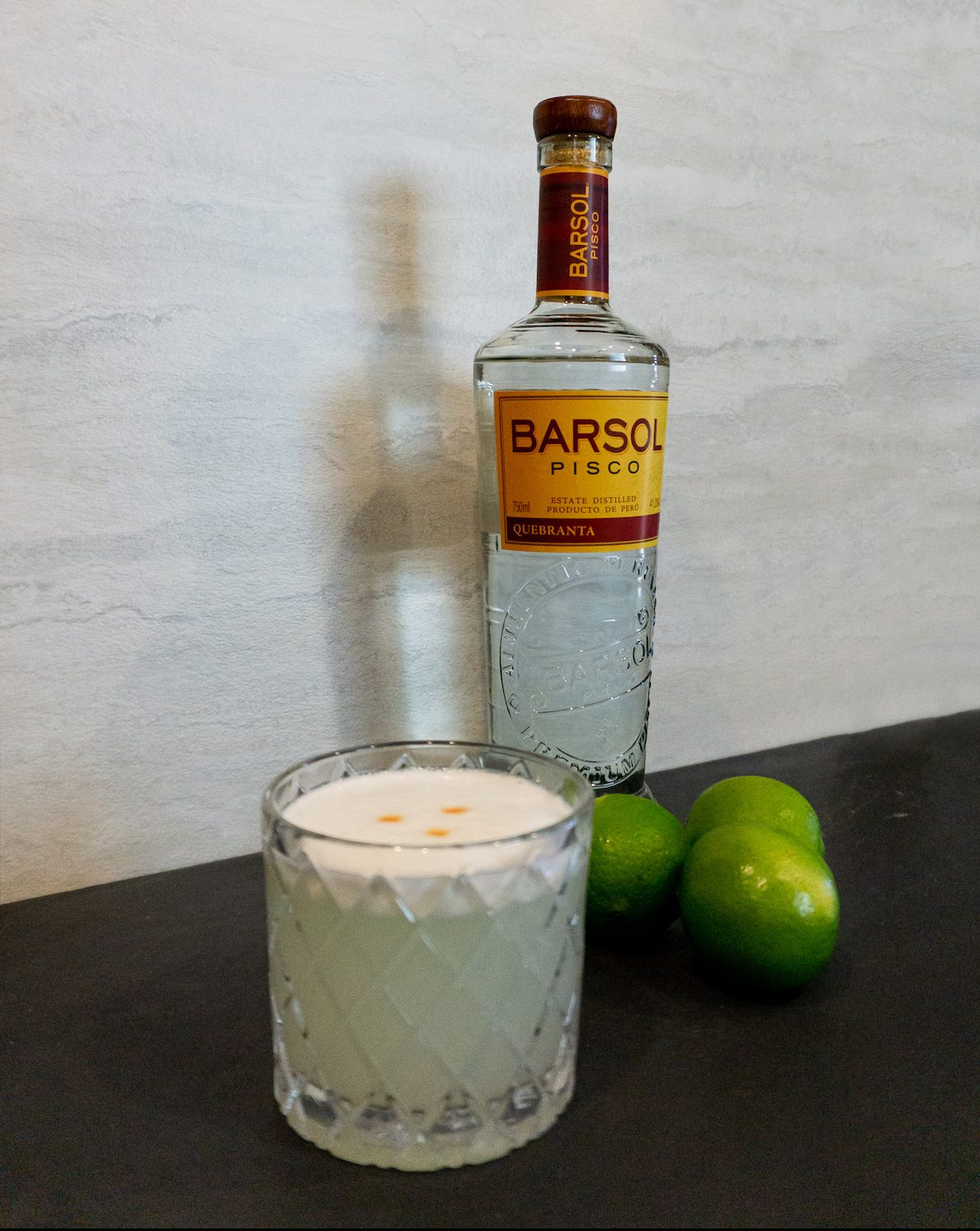 pisco sour cocktail in rocks glass with lime barsol pisco bottle