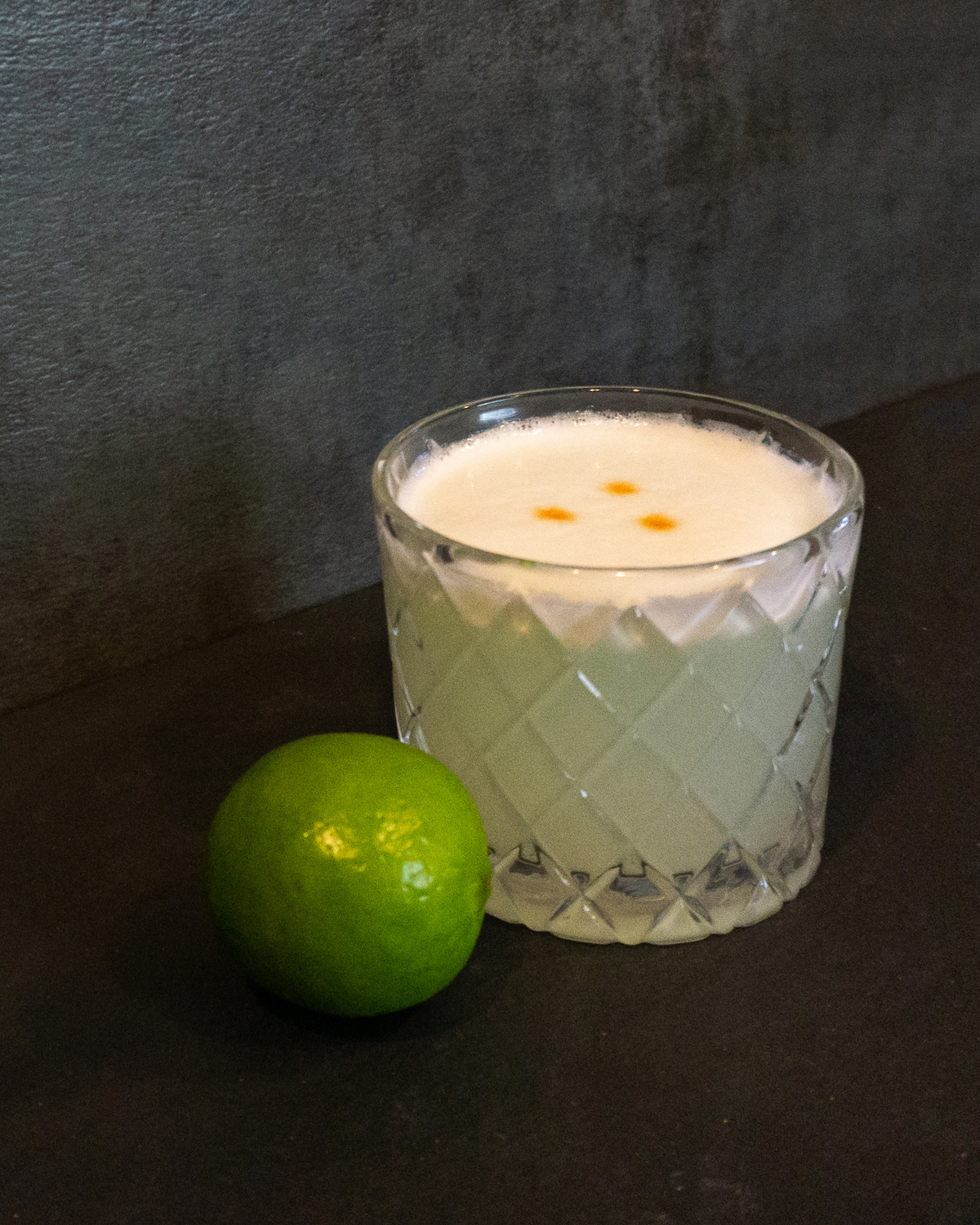 pisco sour cocktail in rocks glass with lime