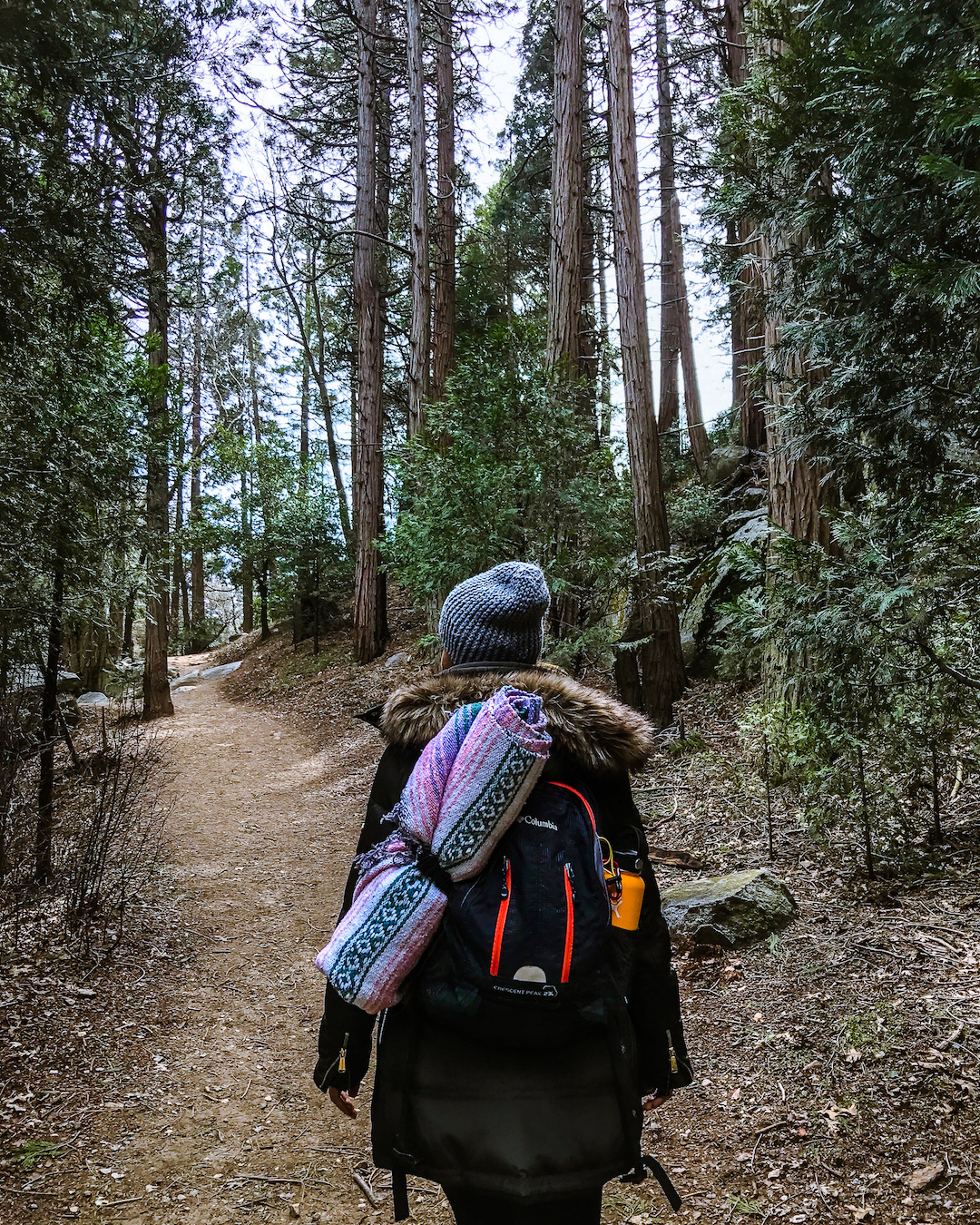 woman hiking in woods with backpack wearing beanie