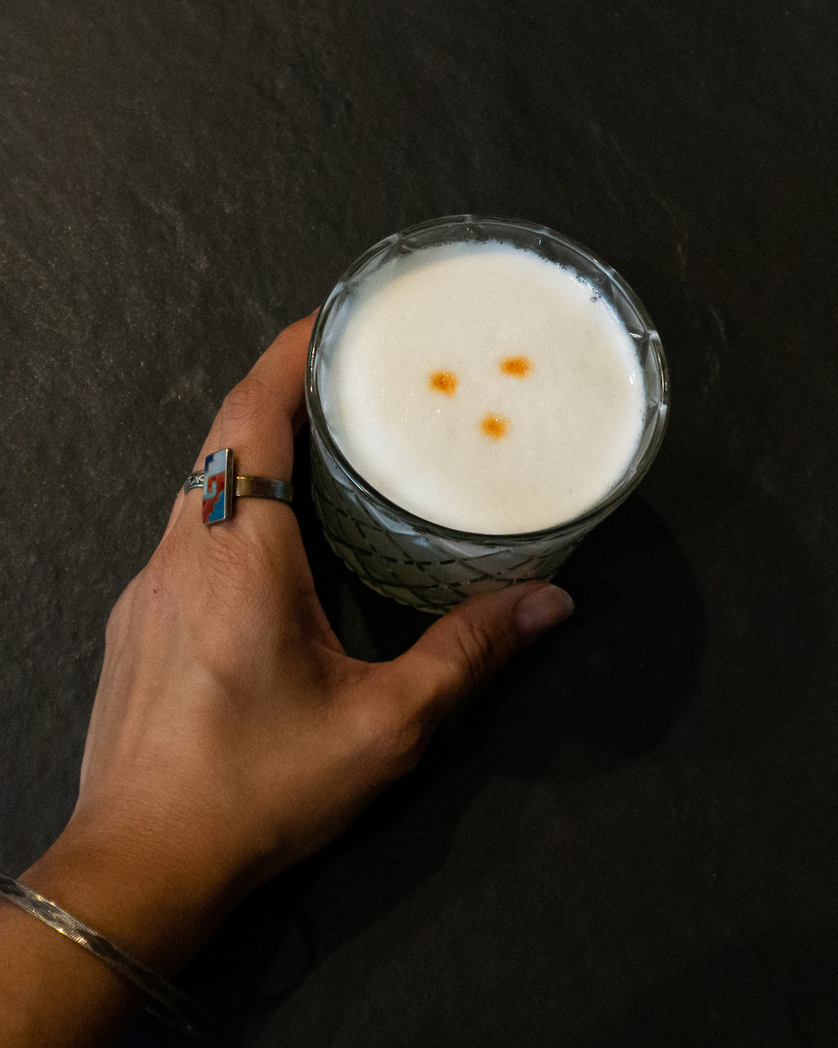 womans hand holding pisco sour cocktail in rocks glass