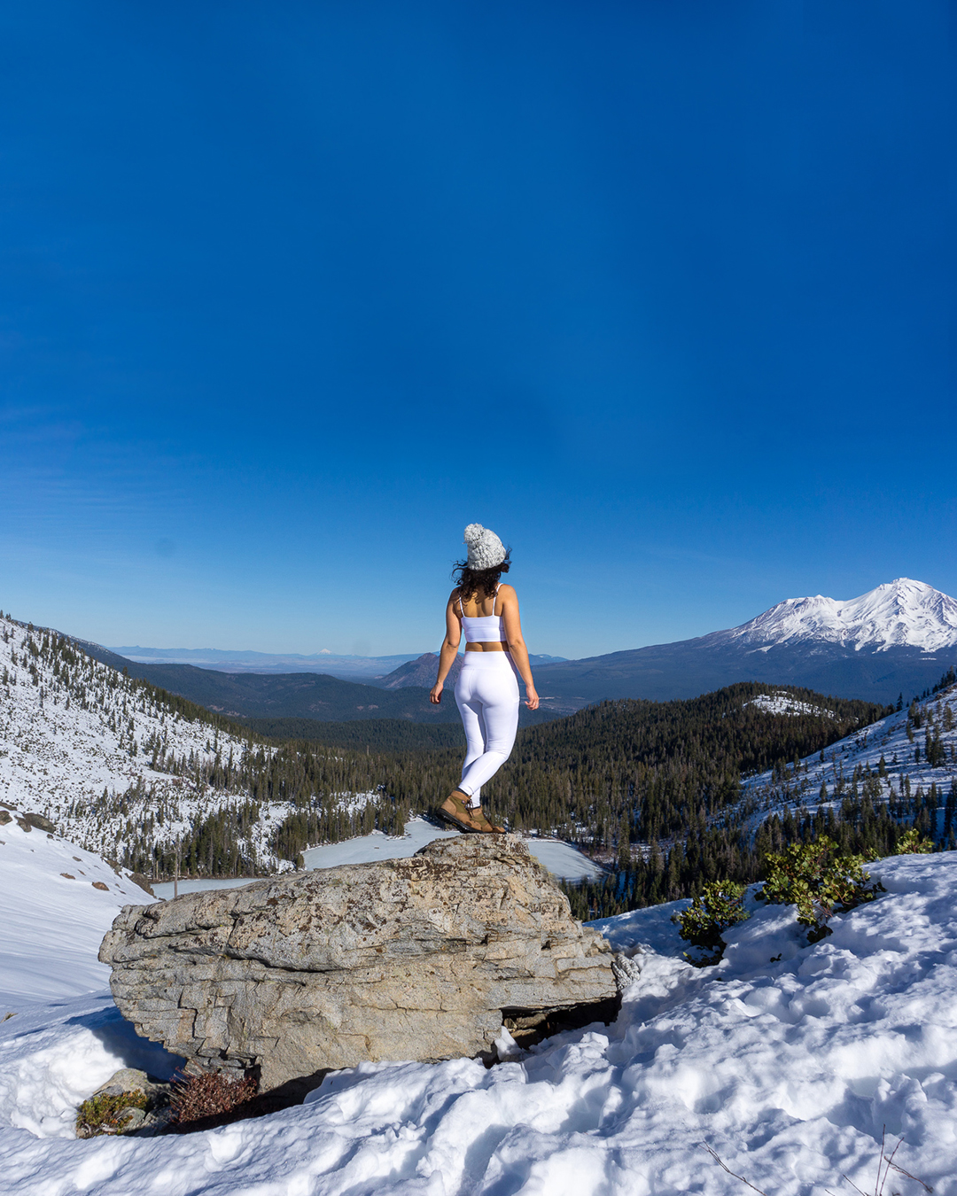 woman at mountain top with view of mount shasta