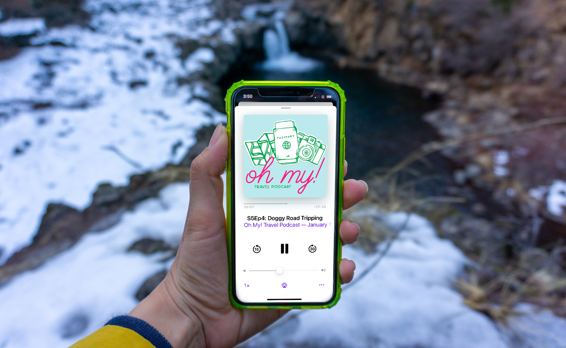 female hand holding iphone with podcast on screen at waterfall with snow