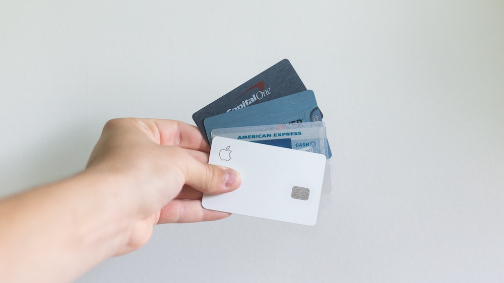 person holding four credit cards