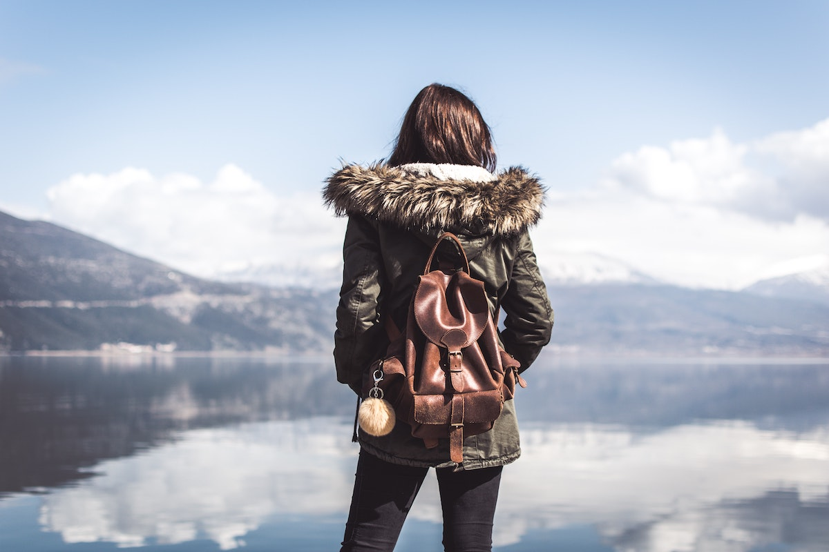woman wearing a jacket and backpack at lake with reflection