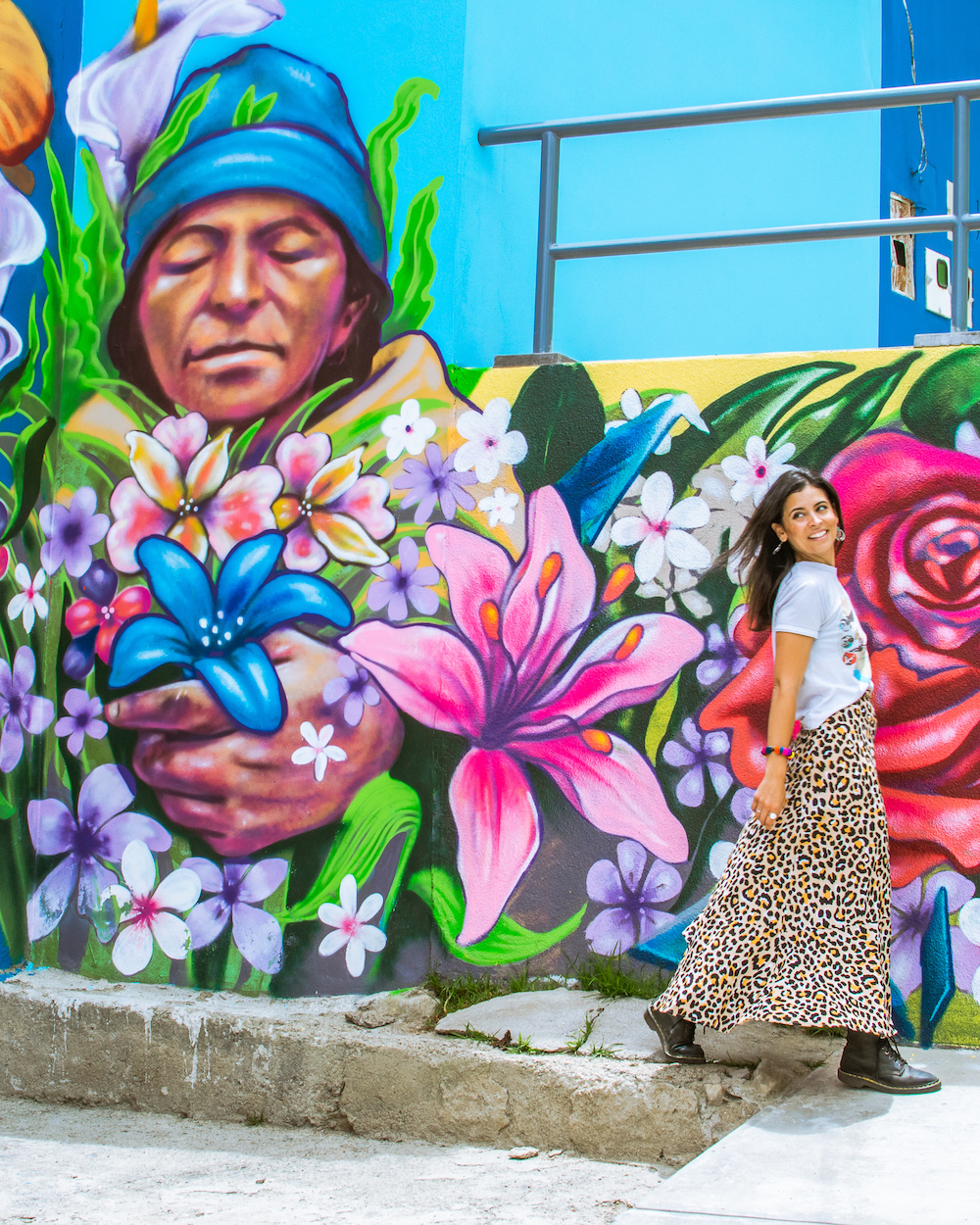 woman walking in color neighborhood with vibrant mural