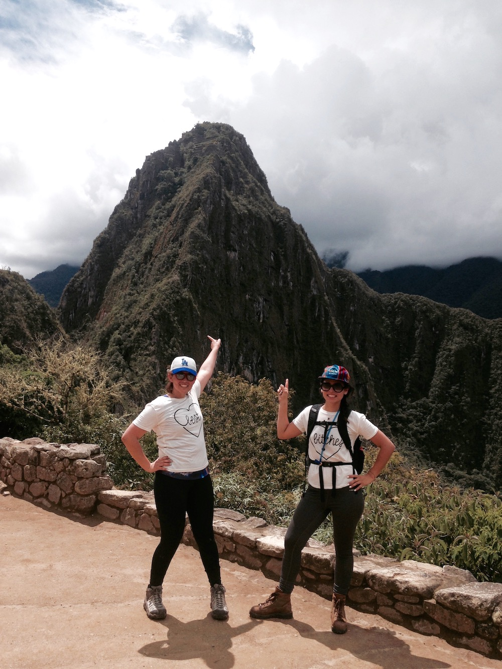 two women in matching white t-shirts standing in front of Huayna Picchu