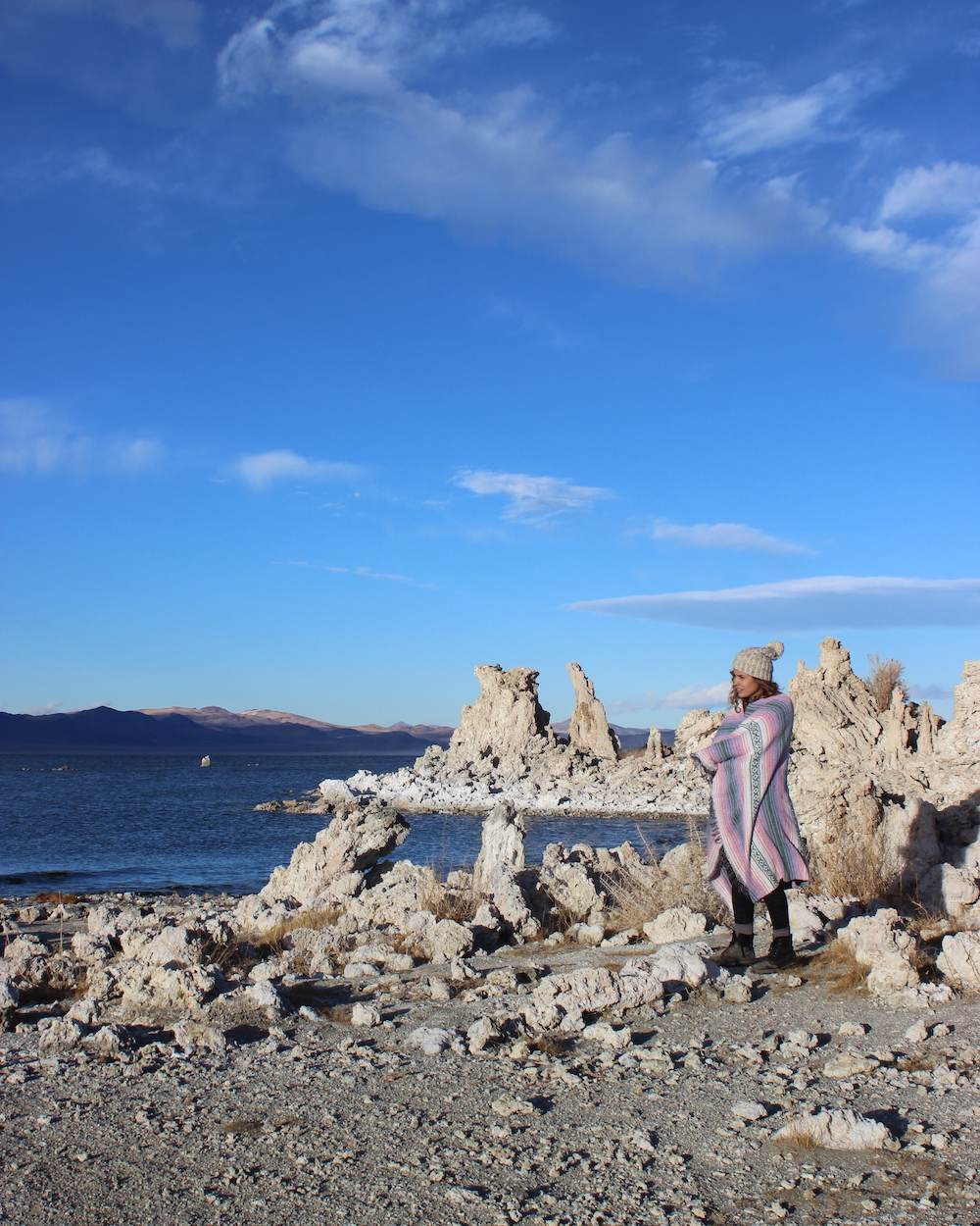 woman in blanket and beanie at mono lake south tufa winter