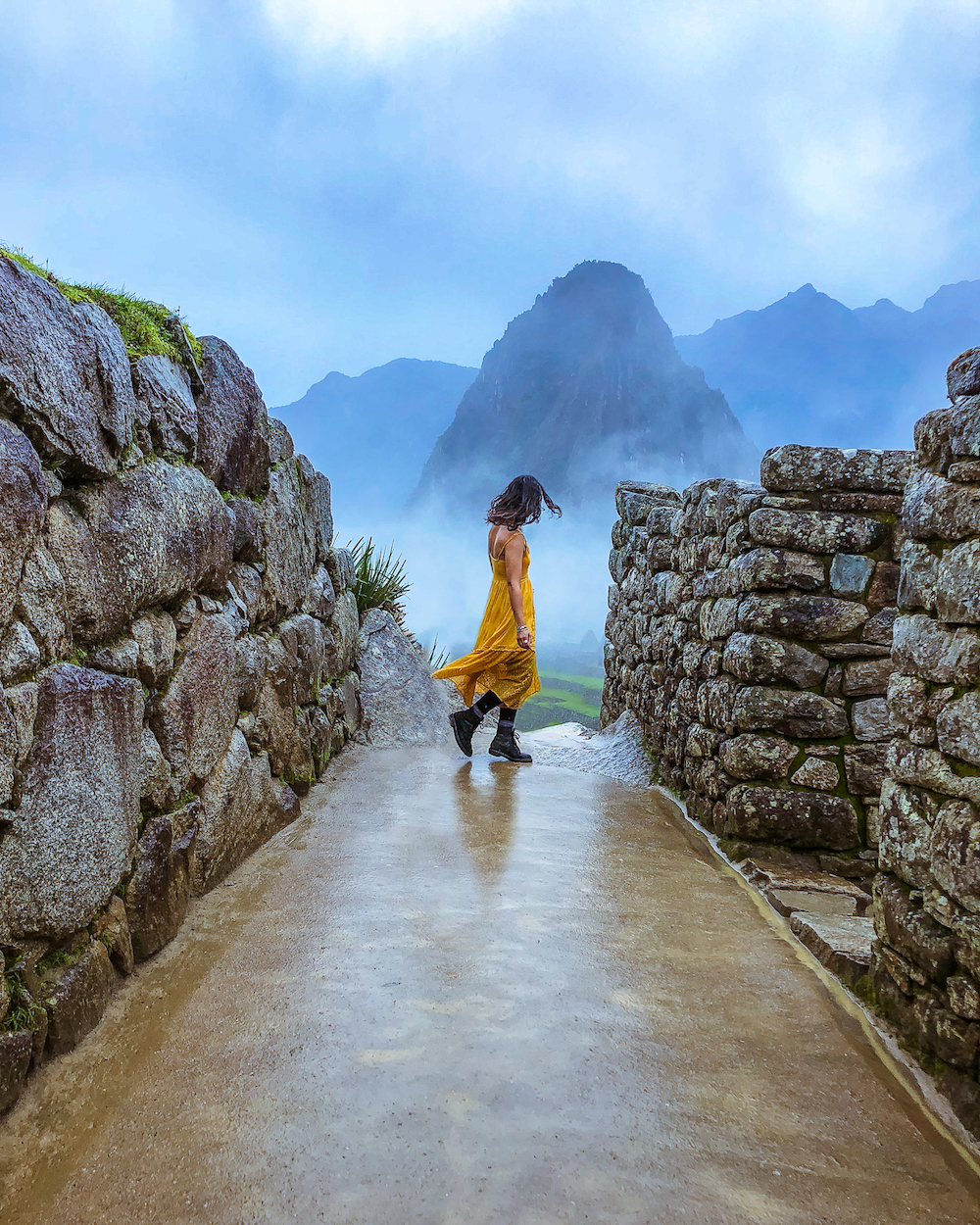 woman in yellow dress at machu picchu overcast cloudy