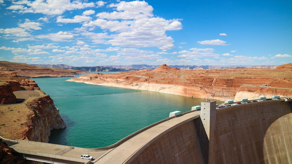 teal water in glen canyon dam in page arizona with blue skies and some clouds