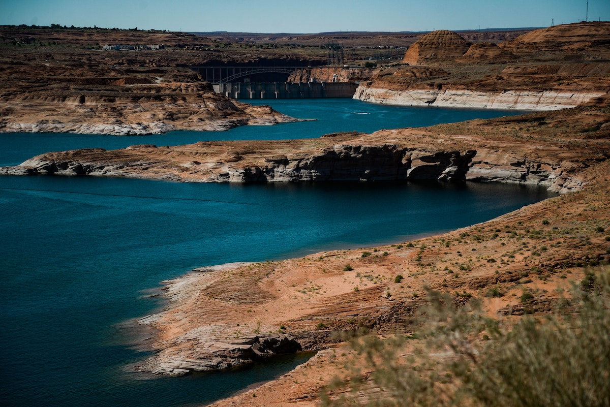 teal water in glen canyon dam in page arizona with with glen canyon bridge in distance