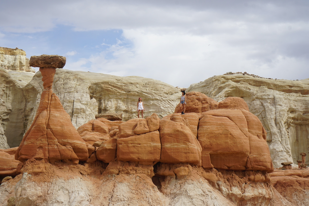 two women standing at edge of toadstool hoodoos while hiking in utah