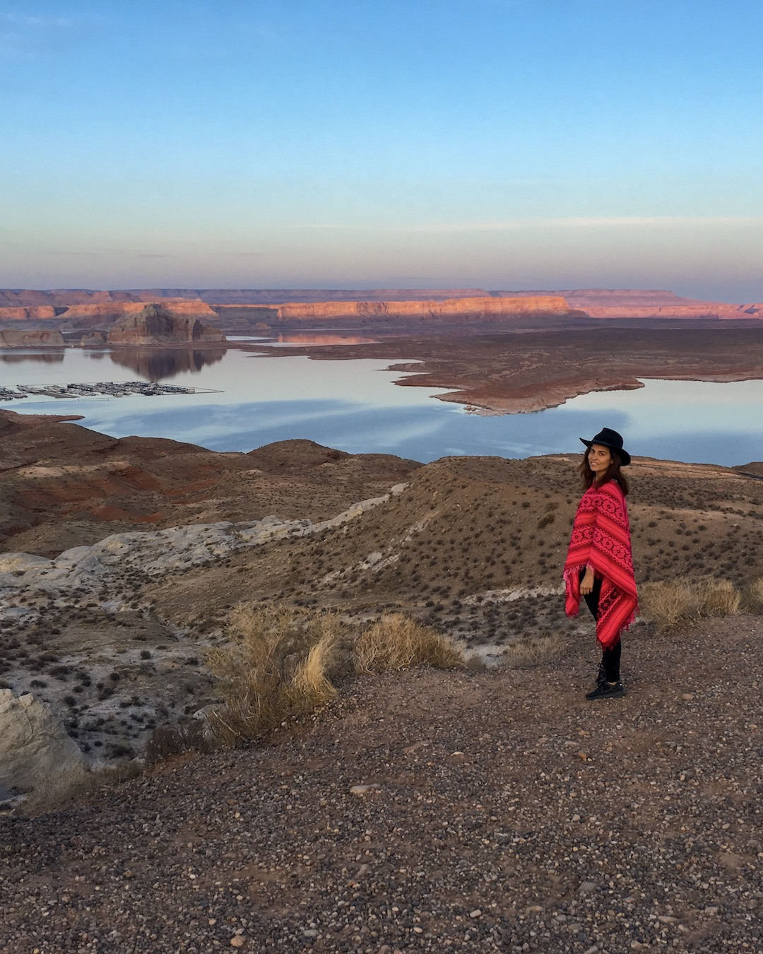 woman in pink poncho at wahweap overlook in Page arizona during a colorful sunset of pink and purple