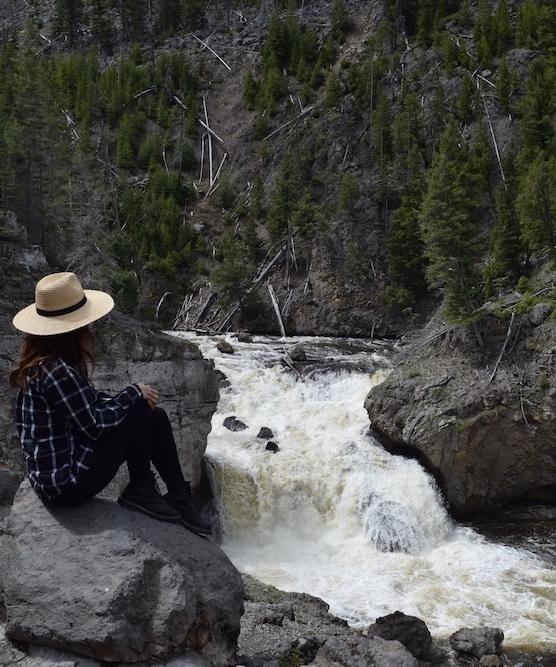 woman at firehole falls waterfall at yellowstone national park