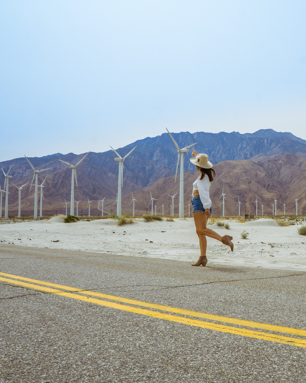 woman in western hat having a photoshoot at palm springs windmills