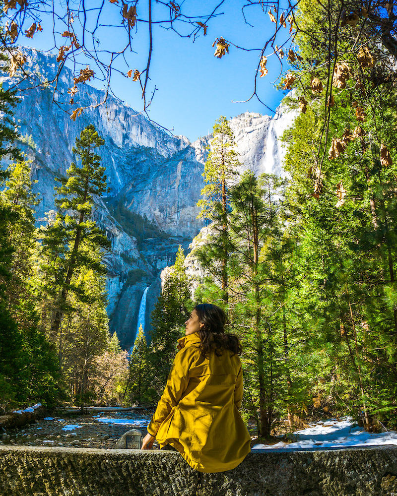 woman in yellow jacket with view of yosemite falls