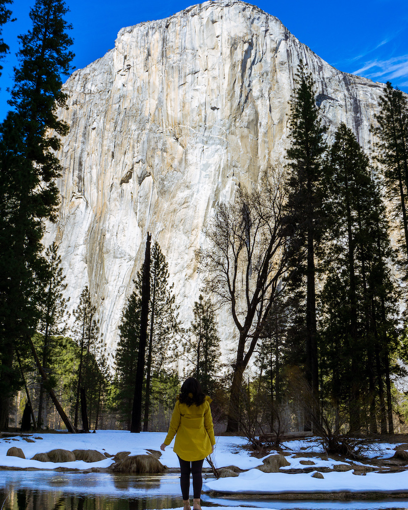 woman on merced river in yellow jacket staring at el capitan in yosemite national park
