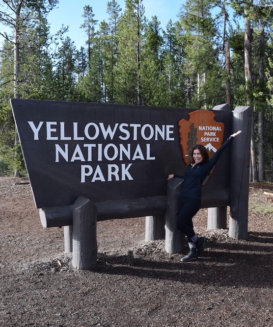 woman in black hiking outfit at yellowstone national park entrance sign best time to visit