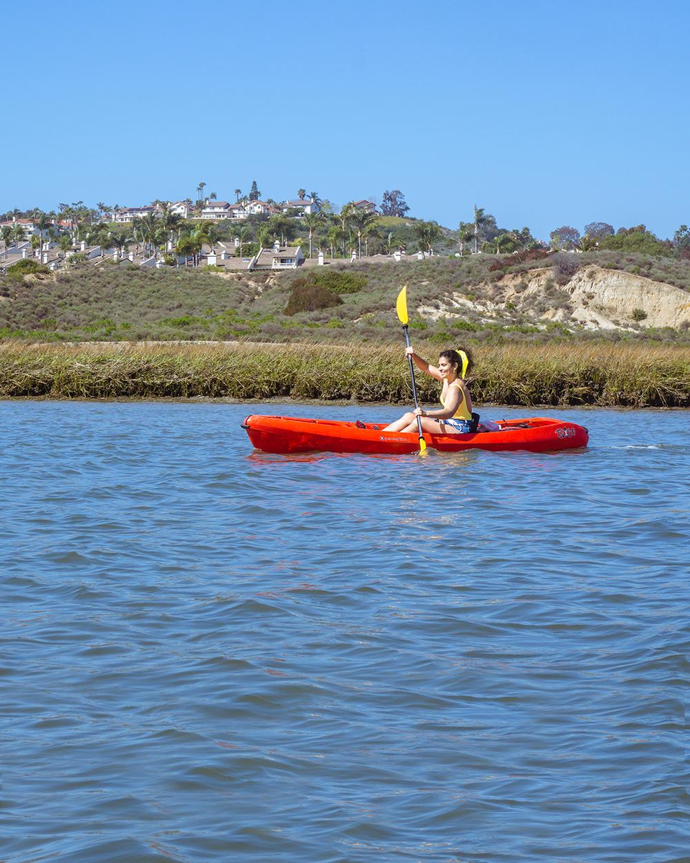 woman kayaking lagoon agua hedionda in carlsbad ca