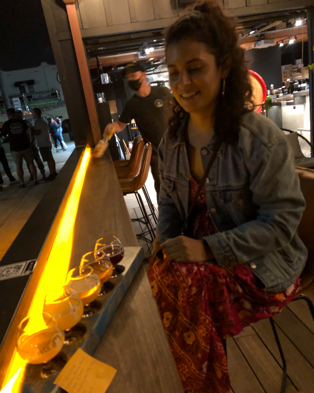 woman drinking pure project flight carlsbad breweries can diego county