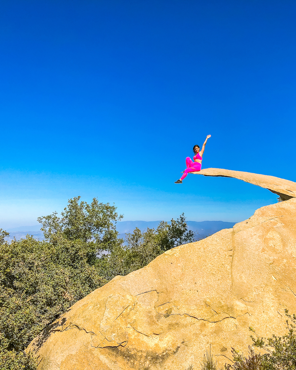 woman in hot pink outfit sitting on potato chip rock cliffin san diego hikes