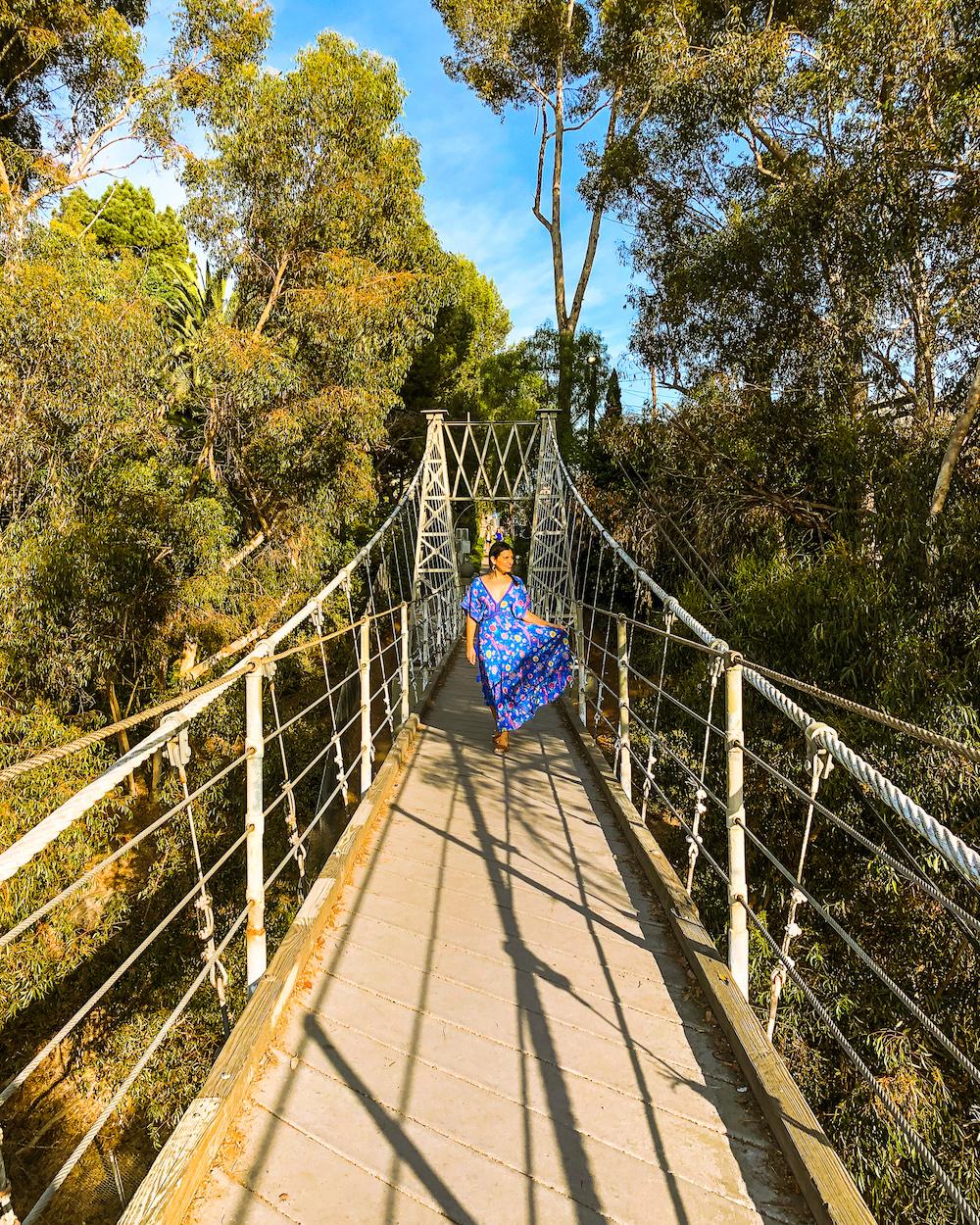 woman crossing suspension bridge