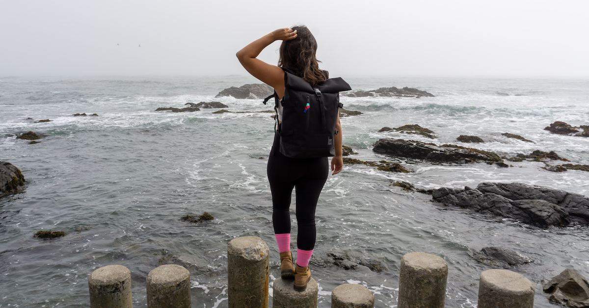 woman wearing a black backpack looking into the ocea