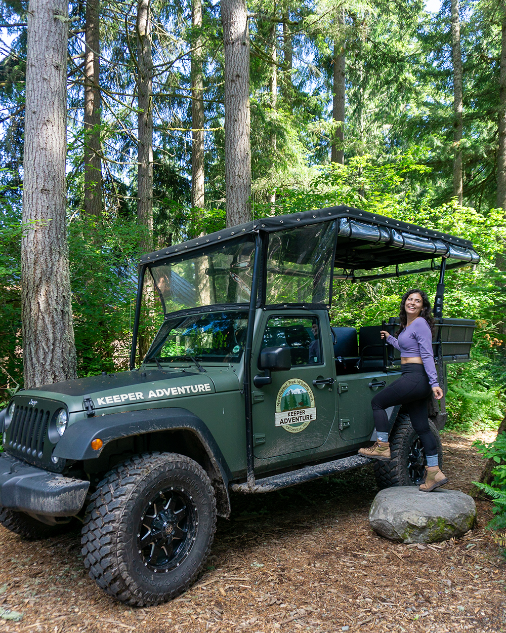 woman standing by forest green outfitted jeep at northwest trek wildlife park