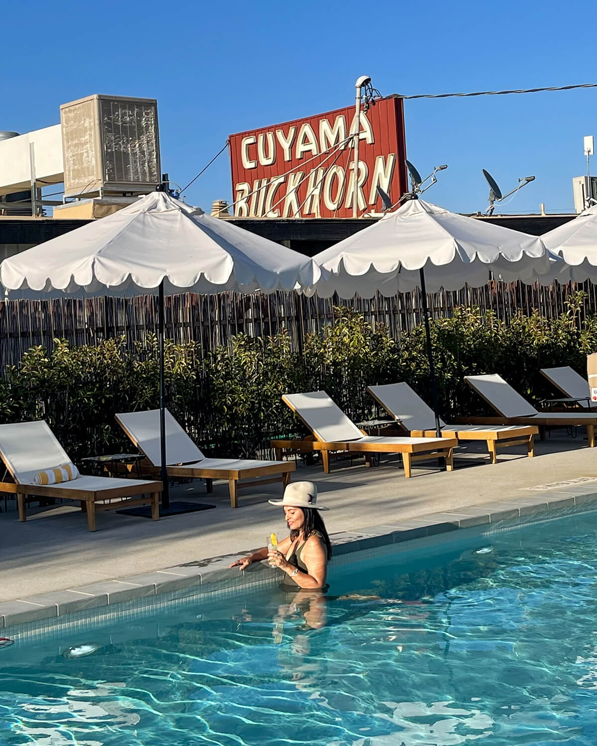 woman in pool at cuyama buckhorn hotel holding drink