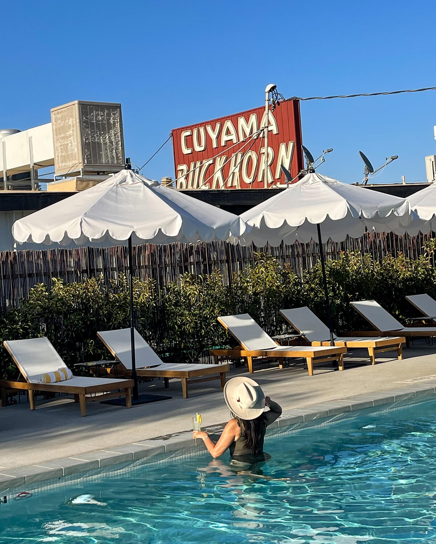 woman in pool holding drink cuyama buckhorn hotel california